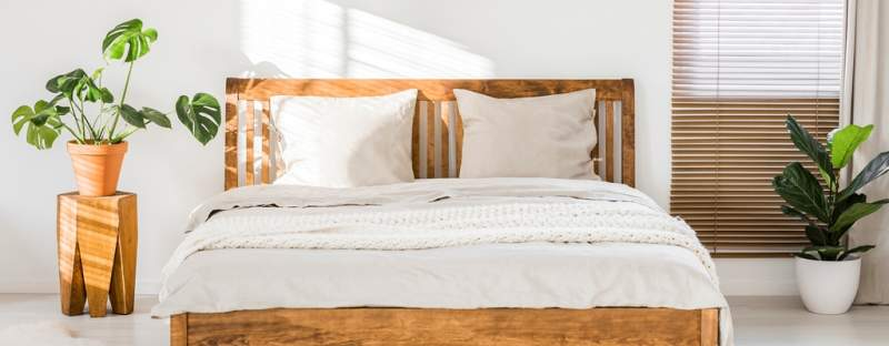 close-up-of-double-wooden-bed-with-bedding