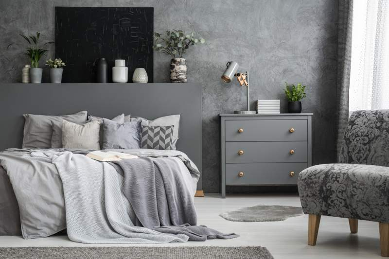 grey-armchair-near-cabinet-and-bed-with-sheets