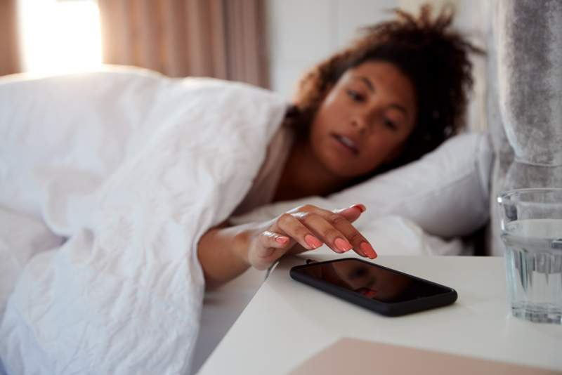 woman-waking-up-in-bed-reaches-out-to-turn-off