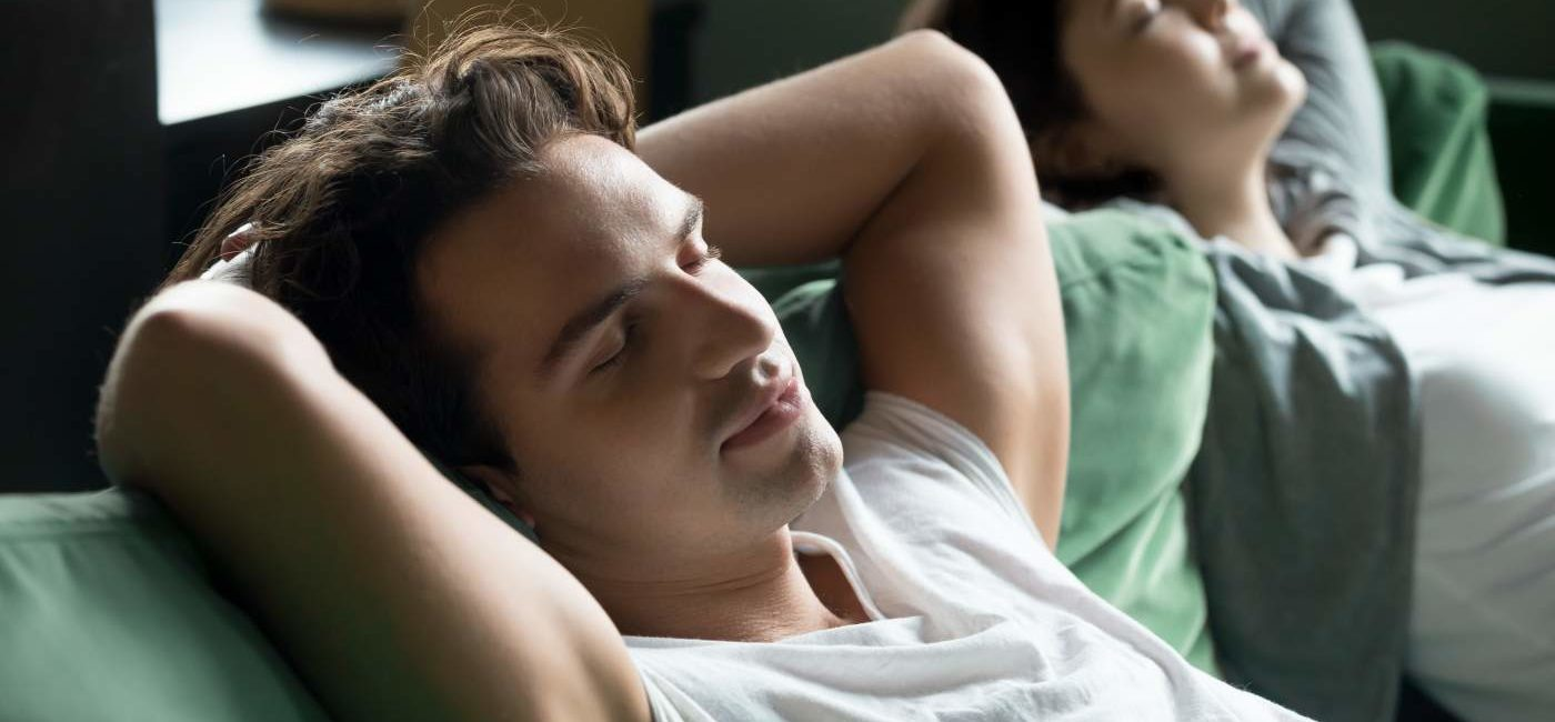 Young man relaxing on comfortable couch with girlfriend at home