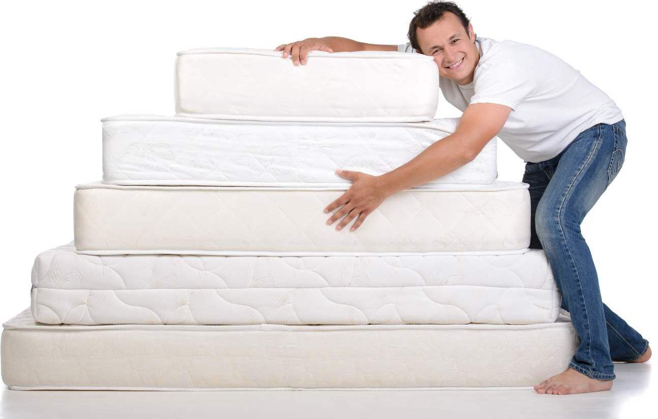 Funny man in pajamas sitting on lots of mattresses