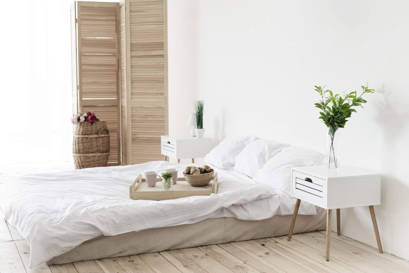 Tray with breakfast on bed in bright bedroom